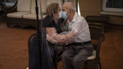 Una mujer abraza y besa a su marido a través de una pantalla de plástico para evitar contraer el coronavirus en una residencia de ancianos en Barcelona.