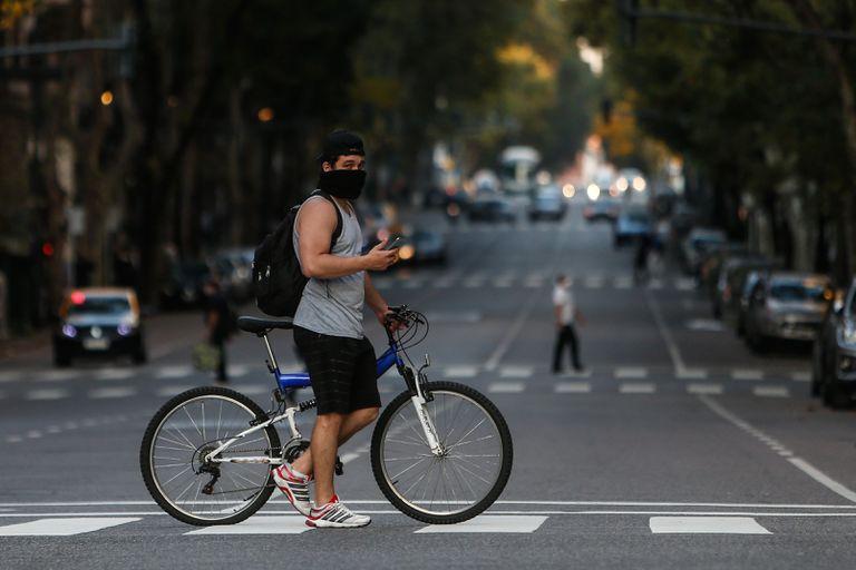 Un hombre que usa un tapabocas cruza la Avenida de Mayo en su bicicleta, este lunes, al cumplirse un mes de la cuarentena obligatoria por el virus COVID-19, en Buenos Aires (Argentina).