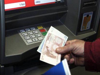 Un hombre retira euros de un cajero automático.