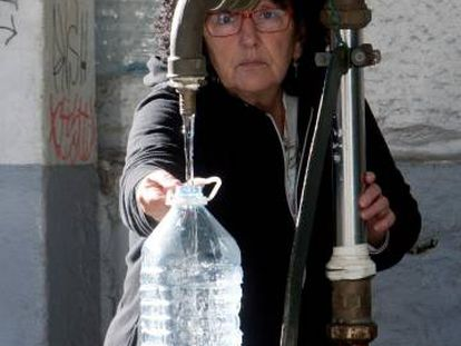 Una vecina de Vigo se abastece de agua potable en una fuente pública.