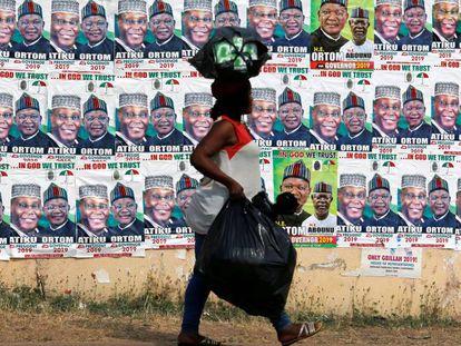 Una mujer camina junto a una pared con carteles de campaña del opositor Partido Popular Democrático, el 26 de enero en Makurdi, en el Estado de Benue.