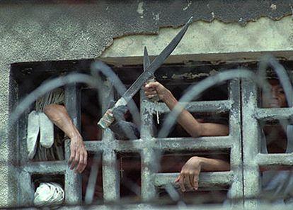 Presos de la cárcel de La Planta, en Caracas, exhiben cuchillos durante un motín, en 1996. En éste y otros 15 centros venezolanos cumplen condena 111 españoles.