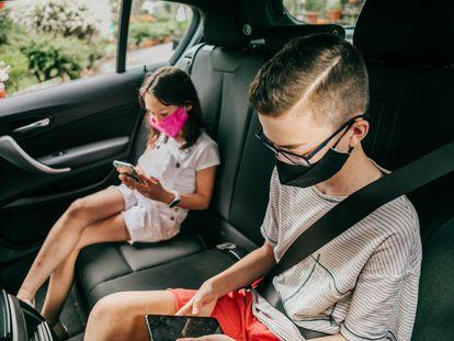 Dos niños usan sus móviles en un coche.