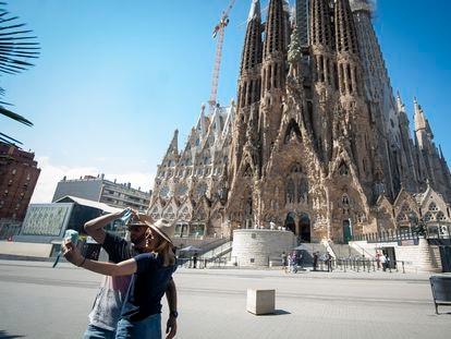 Una pareja se fotografía ante una Sagrada Familia casi vacía en Barcelona.