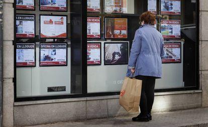Una mujer mira el escaparate de una agencia inmobiliaria en Terrassa (Barcelona), el pasado marzo.