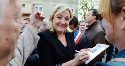 La candidata del Frente Nacional a la presidencia francesa, Marine Le Pen firma autógrafos hoy frente a una exoficina de la Gendarmeria en Brienon-sur-Armanon, en el dentro de Francia.