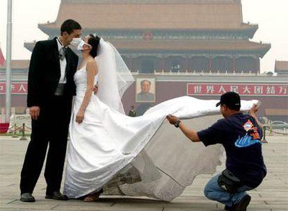 Es más difícil que cuajen cambios en costumbres sociales arraigadas que en cuestiones meramente higiénicas. En la imagen, unos novios se besan con la mascarilla puesta, en Pekín.