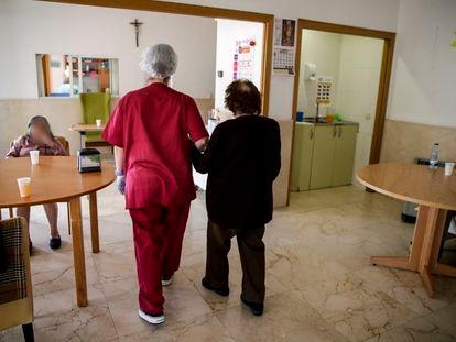 Una empleada ayuda a una señora mayor a caminar en la residencia de ancianos Santa María de Montecarmelo, en Madrid.
