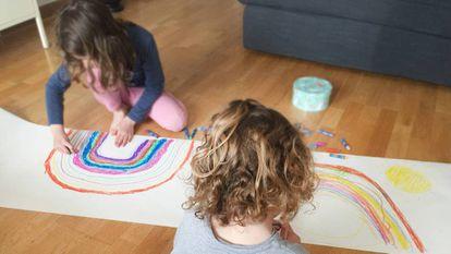 Dos niños dibujan en casa arcoíris solidarios.