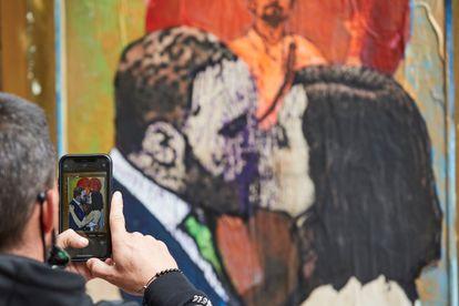 """Una persona fotografía con su teléfono el grafiti """"Lo que el beso se llevó"""", una obra del artista urbano TvBoy en la que aparecen pintados Santiago Abascal, Isabel Díaz Ayuso y Pablo Iglesias."""