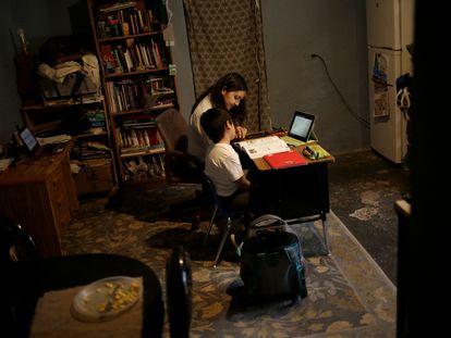 Amalia Rodríguez acompaña a su hijo Luciano Rodríguez, de 7 años, asiste a una clase que se realiza en línea en Ciudad Juárez, México.