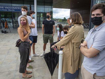 Un grupo de jóvenes universitarios de San Sebastián esperan en el exterior del centro de vacunación de Biarritz (Francia).