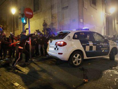 Varios manifestantes, con las caras tapadas, junto al coche de la Policía Municipal atacado el 14 de diciembre de 2013 en el centro de Madrid.