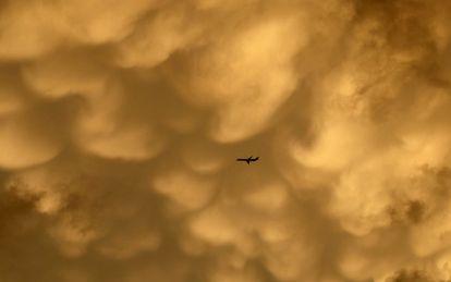 Un avión vuela hacia el aeropuerto internacional de O'Hare bajo un mar de nubes, en Chicago.