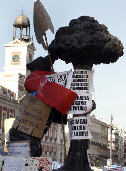 El oso y el madroño de la madrileña Puerta del Sol permanece forrado con carteles con diversos lemas.