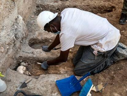 Un operario rescata los restos humanos hallados a los pies de la muralla árabe de Valencia.