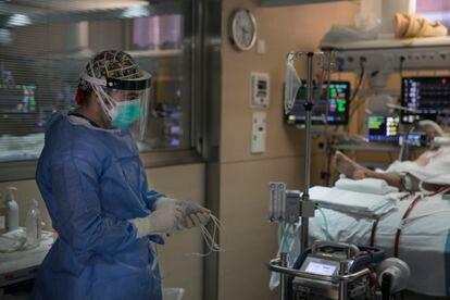 Un sanitario atiende a un paciente en la UCI del Hospital Vall d'Hebron de Barcelona.