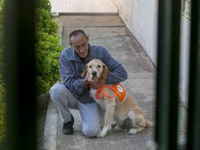 Emilio, un recluso del centro penitenciario Madrid III (Valdemoro), con uno de los perros que cuida, este martes.