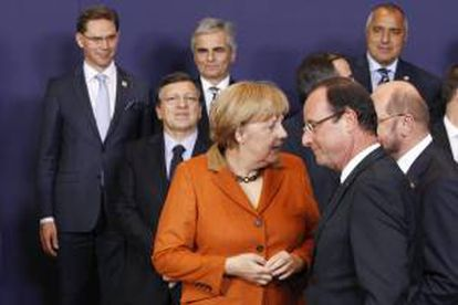 La canciller alemana Angela Merkel (i) conversa con el presidente francés François Hollande (d) durante la foto de familia de la cumbre de jefes de Estado y de Gobierno de la Unión Europea (UE) en Bruselas, Bélgica, hoy, jueves 18 de octubre de 2012.