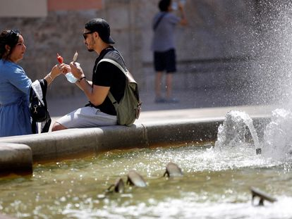 Dos personas se toman un helado junto a una fuente en Valencia.