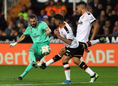 Benzema remata a portería ante Garay y Costa.