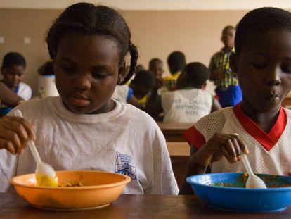 Unos niños comen en el comedor de su colegio en Ghana.