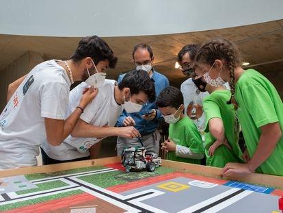 Tres miembros del jurado verifican si el robot de los concursantes ha funcionado correctamente durante el torneo de robótica, en Cáceres.