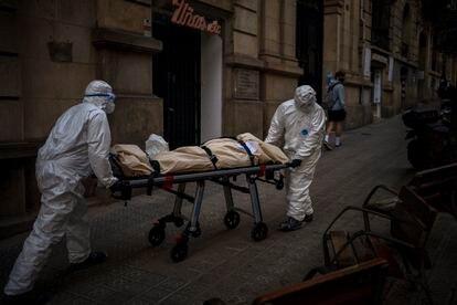 Empleados de una funeraria trasladan el cadáver de un anciano fallecido por covid en una residencia de Barcelona, el 13 de noviembre.
