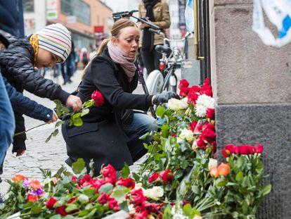 Un grupo de ciudadanos colocan flores en homenaje a las víctimas del atentado.