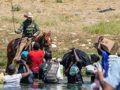 Un agente fronterizo amenaza con una soga a un grupo de migrantes en el río Grande, entre Texas y México, este 19 de septiembre.