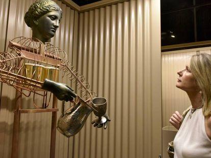 Una visitante de la exposición sobre robots en CosmoCaixa, frente a una réplica de la sirviente autómata de Filón de Bizancio.