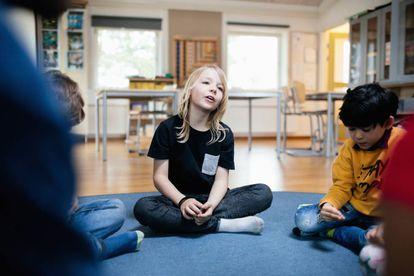 Varios niños celebran una asamblea en el aula.