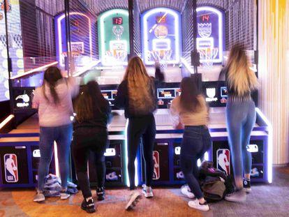 Un grupo de chicas juega en unos recreativos.