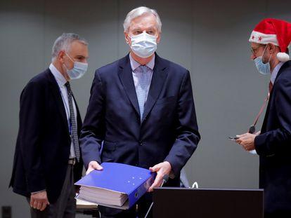 El negociador comunitario Michel Barnier (en el centro) deposita en la mesa el archivador con los cientos de páginas del acuerdo alcanzado con el Reino Unido en presencia de delegados griegos, durante la reunión extraordinaria convocada este viernes en Bruselas para explicar los detalles del acuerdo del Brexit.