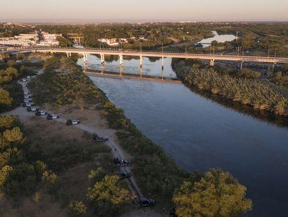 Una hilera de vehículos de la policía municipal de Ciudad Acuña custodia el Río Bravo frente al puente internacional de Del Río, este jueves.