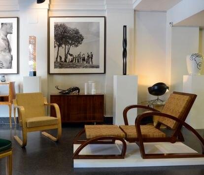 A la izquierda, el sillón 402 de Alvar Aalto (el diseño original es de 1933). A la derecha, la 'chaise-longe' 'art decó' en dos piezas de Francis Jourdain (1930). Las fotografías que hay expuestas al fondo son de Nicolás Müller.
