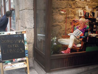 La protagonista de la acción lee un libro de Paul Krugman en el escaparate.