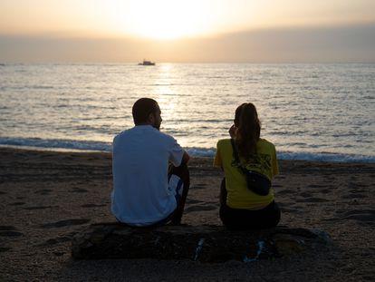Una pareja observa el mar en una playa de Barcelona.