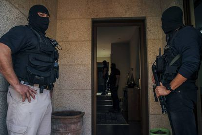Dos policías custodian la entrada de la vivienda de Pontevedra mientras sus compañeros registran el interior.