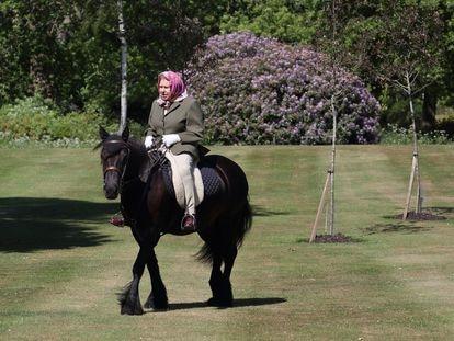Isabel II, a caballo por los jardines del castillo de Windsor.