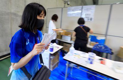 Una voluntaria de la organización de los Juegos Olímpicos distribuye una prueba para detectar la covid-19 a través de la saliva, este sábado.
