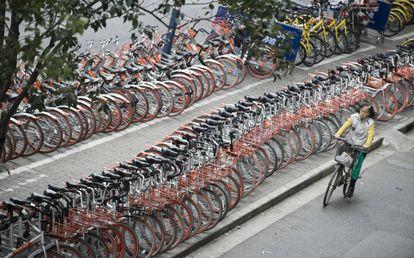 Una señora pasa frente a hileras de bicicletas de pago por uso en Shanghái.