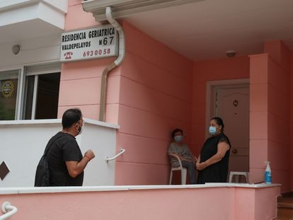 José Ángel Serrano visita a su madre Angustias, sentada, vigilados por una cuidadora Gilmar en el porche de la residencia de mayores Valdepelayos 67, en Leganés. KIKE PARA.