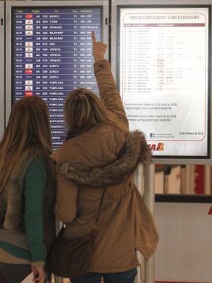 Dos mujeres miran los paneles de información en Barajas