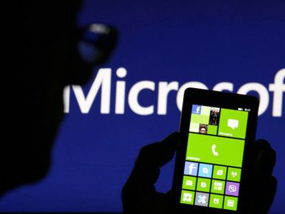 Un hombre con su Nokia Lumia, ante un cartel de Microsoft.