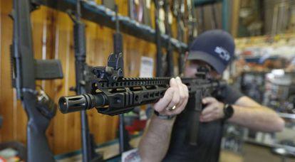 Un hombre sostiene un AR-15 en una tienda de armas.