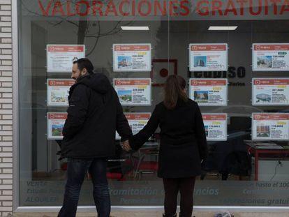 Una pareja mira un escaparate con anuncios de pisos en el Ensanche de Vallecas (Madrid).