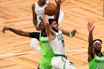 Jayson Tatum se dispone a anotar entre dos jugadores en el Celtics-Timberwolves.