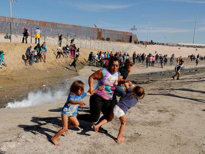 Una mujer migrante hondureña, huye de gases lacrimógenos frente al muro fronterizo entre Estados Unidos y México en noviembre de 2018.