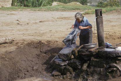 Una mujer lava ropa en el abrevadero de un pueblo en la sierra ecuatoriana.